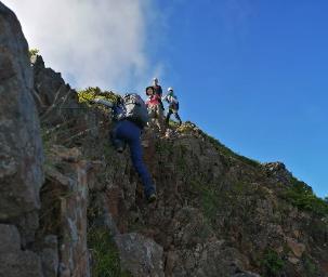 岩山を登っている人  自動的に生成された説明