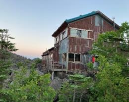 山の中の家  自動的に生成された説明
