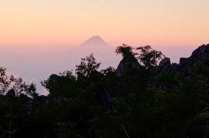 夕日に映る森と山  自動的に生成された説明